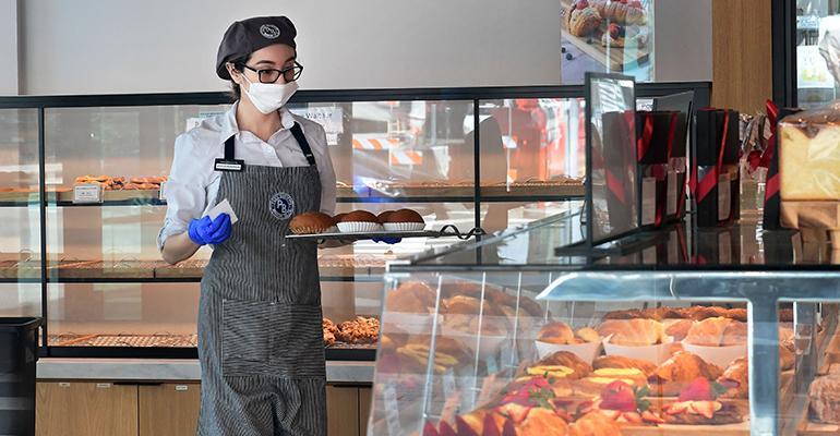 Restaurant worker wearing mask in a bakery