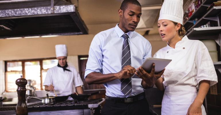Male manager and female chef using digital tablet in kitchen.jpg