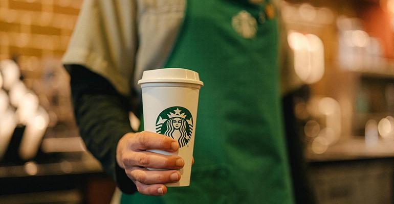 Starbucks barista with coffee cup