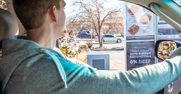 A consumer using a Valyant AI menu board drive-thru