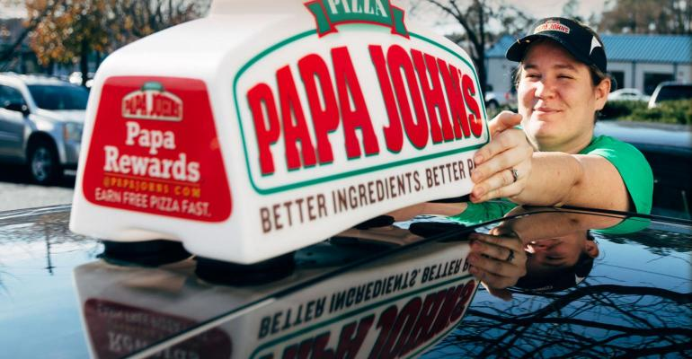 A Papa John's employee at a delivery vehicle