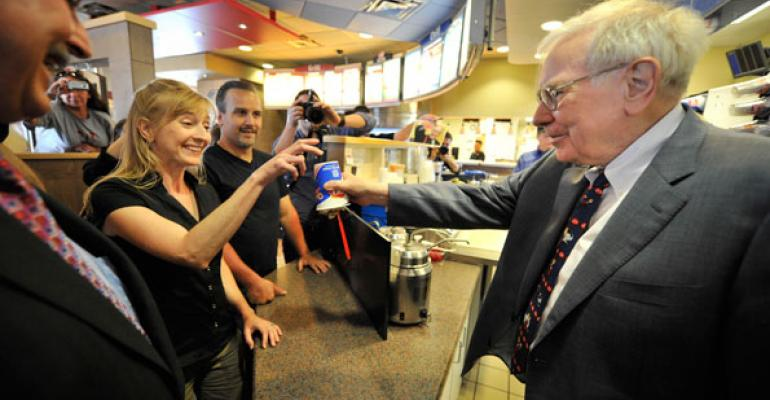 Famous investor Warren Buffet right serving the first Smores Blizzard at a Dairy Queen location in Omaha Neb