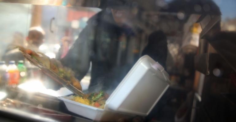 A New York City food cart worker fills a plastic foam container with food for a customer