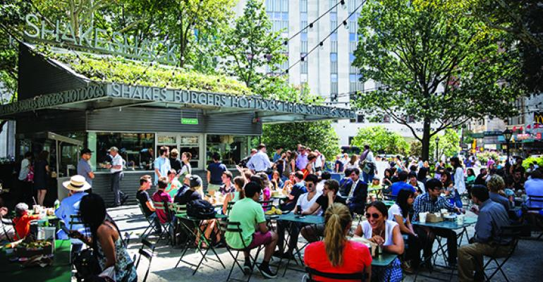 People sit outside Shake Shack in Madison Square Park in New York City