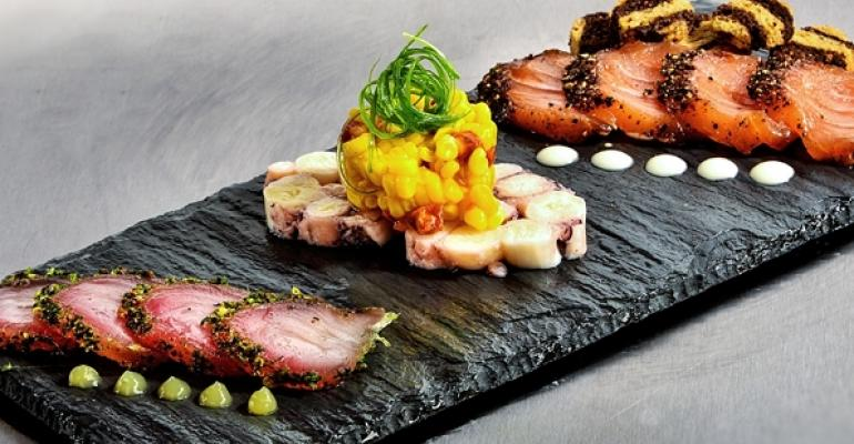 From left Herbcured kampachi with cilantrolime crema octopus torchon with pickled corn and chorizo and salmon pastrami with Thousand Island aoli and toasted rye bread
