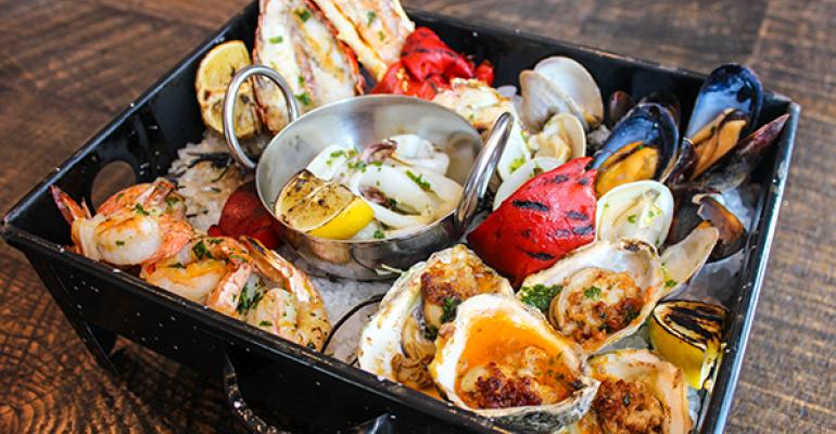 Oysters get grilled torched and served in a special smoke box at Del Campo in Washington DC